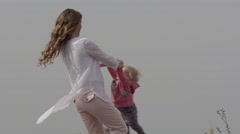Cheerful mother rotating twisting making circle with her little daughter - stock footage