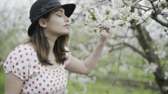 young woman dressed in retro style tastes cherry blossom flavour slow motion - stock footage