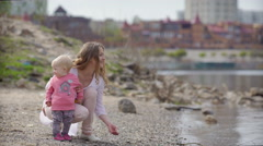 Mother and child on a river bank Stock Footage