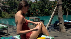 Sexy woman applying sunscreen on legs sitting on subed by pool Stock Footage