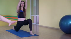 Fitness class and instructor stretching legs in bright room 4k Stock Footage