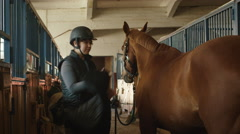 Young jockey girl is preparing a horse for a ride in stable - stock footage