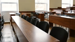 Empty lecture hall at the university with brown desks, blackboard and rostrum wi Stock Footage