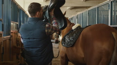 Stableman is preparing a horse for a ride in stable Stock Footage