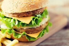 Close up of hamburger or cheeseburger on table Stock Photos