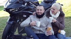 Happy young couple having picnic with coffee near cycle Stock Footage