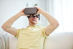 young man in virtual reality headset or 3d glasses - stock photo