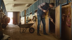 Man is cleaning a stable from hay with a pitchfork Stock Footage