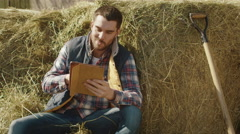 Farmer is sitting in hay and using a tablet computer Stock Footage