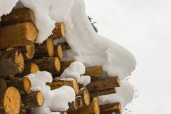 Stacked wood covered with snow, alps Austria in Salzburg Stock Photos