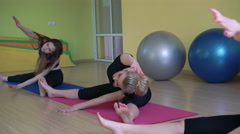The girls stretching legs synchronously sitting on the splits in gym 4k - stock footage