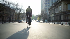 Back view man rides a bicycle down the empty street in sun light slow motion Stock Footage