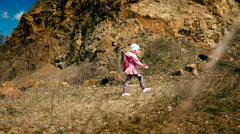 Little girl hiker in a pink jacket with a backpack walks in the canyon Stock Footage