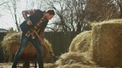 Man is cleaning a farm yard from hay with a pitchfork on a sunny day - stock footage