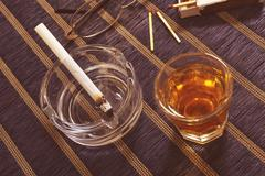 Whiskey and cigarette in ashtray. Stock Photos