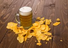 Frothy beer and chips - stock photo