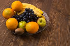 Bananas, oranges, apples, grapes are in dish - stock photo