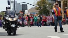 $15.00 per hour crowd of protesters and police in the street in San Diego - stock footage