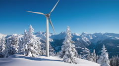 Rotating wind turbine above sunny snowy forest in the mountains 4K footage Stock Footage