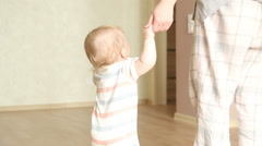 Baby boy 1 year old walking his first steps Stock Footage