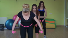 Female girls lifting dumbbels in a gym. 4k Stock Footage