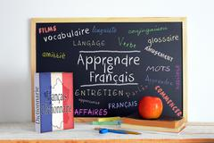 Blackboard with the message LEARN FRENCH (Apprendre Français) - stock photo