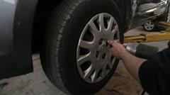 Releasing wheel screws using pneumatic screwdriver - stock footage