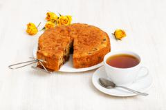 Homemade cake with a piece cut off and cup of tea on white wooden table - stock photo
