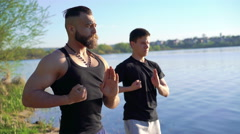 Training exercises of Wing Chun near the river between strong men. 4k Stock Footage