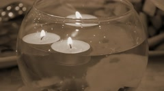 Burning candles floating in a decorative vase retro filtered Stock Footage