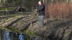 Man draw up fishing rod near river Stock Footage