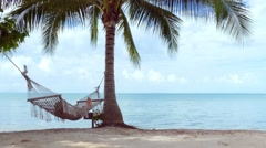 Relaxed woman lying in hammock on the beach Stock Footage