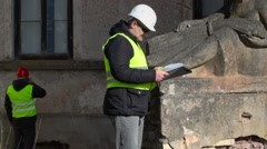 Building inspector checking old monument near building Stock Footage