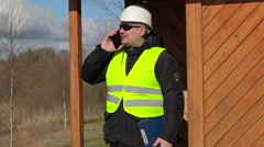 Civil engineer talking on smart phone at the wooden structure of the building Stock Footage