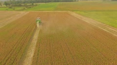 Countryside aerial shot of combine harvester in golden wheat field - stock footage