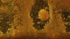 Golden bubbles and foam ascending on black background, close up Stock Footage