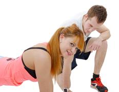 male trainer assisting young woman doing push-up - stock photo