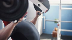 Young man with earphones flexing chest muscles on gym machine Stock Footage