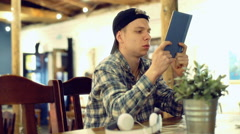 Pensive boy reading book in the cafe and looking absorbed - stock footage