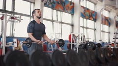 Strong man - bodybuilder with dumbbells in a gym, exercising with a barbell - stock footage