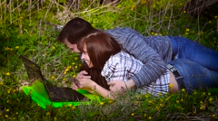 Man gives a woman flowers lying at his laptop Stock Footage