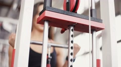 Young woman flexing muscles on cable gym machine. Stock Footage