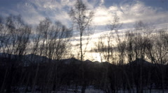 Winter sunset and blue sky against a background of twinkling trees and mountain Stock Footage