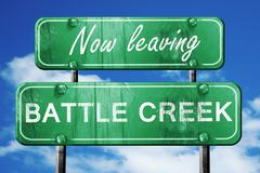 Leaving battle creek, green vintage road sign with rough letteri Stock Illustration