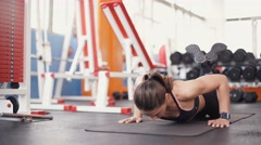 Brunette woman at gym push up push-up workout exercise Stock Footage