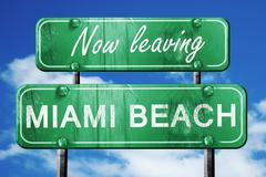 Leaving miami beach, green vintage road sign with rough letterin - stock illustration