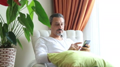 Middle aged guy using mobile phone. Relaxed and sitting on sofa indoor Stock Footage
