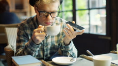 Boy drinking coffee and talking on loudspeaker in the cafe - stock footage