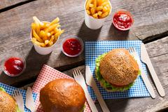 Fresh hamburgers with paper cutlery. - stock photo