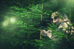 Hunting Poacher in Dense Pine Forest. Hunter in Camouflage with Hunting Rifle - stock photo